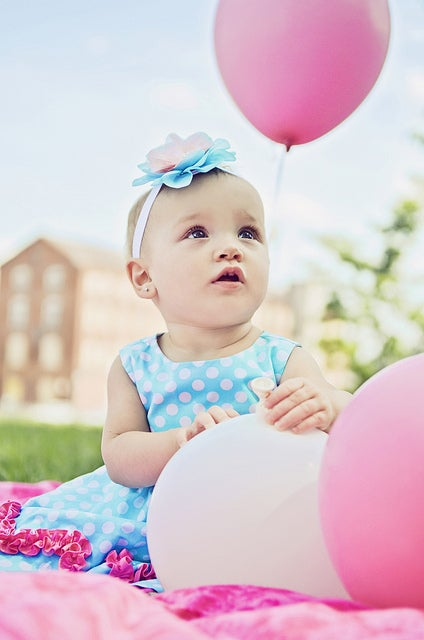 A baby with a pink balloon.