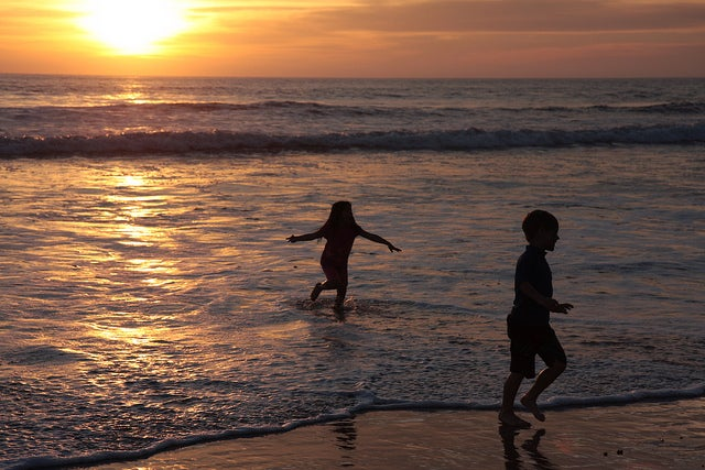 Two children play in the sea as  the sun sets.
