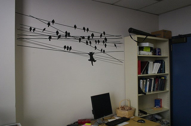 A wall decorated with birds sitting on telephone wires.