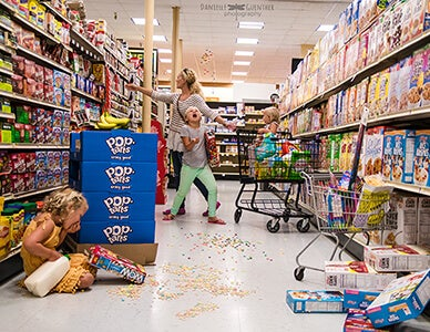 mom with children in cereal aisle