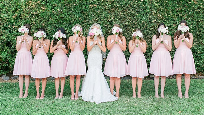 bridesmaids and bride holding up flowers