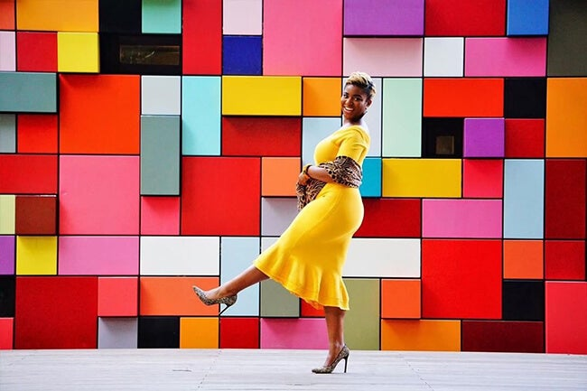 woman in front of colorful wall