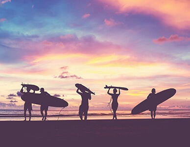 surfers at sunset along beach