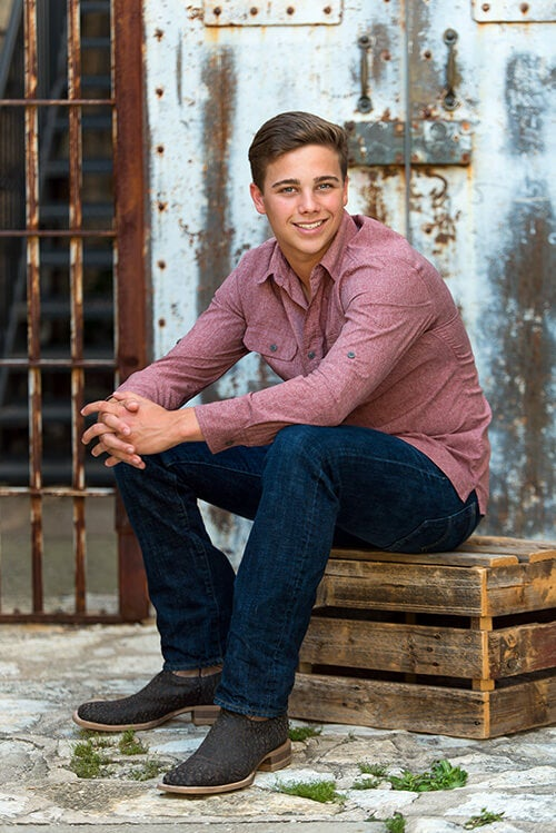 high school senior boy posing on crate