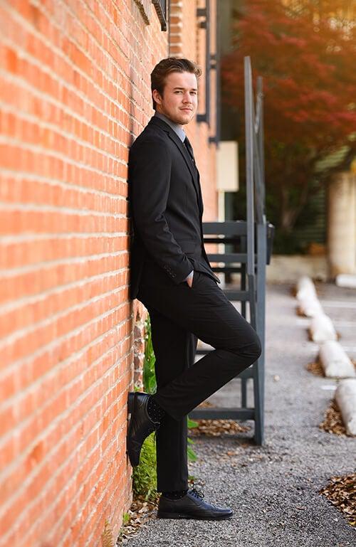 high school senior boy posing against a wall