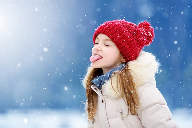 girl sticking tongue out to catch snow