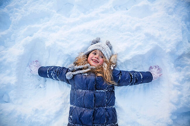 kid making snow angel