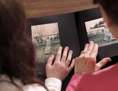 woman looks through photo book by AdoramaPix
