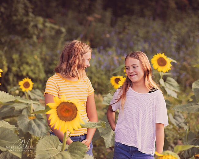 two girls in a sunflower field