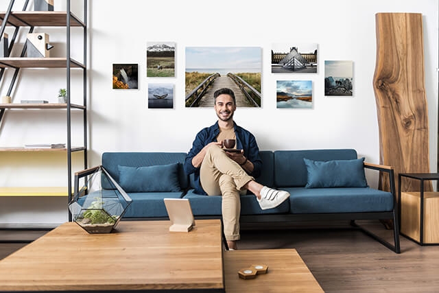 man sitting on couch in front of wall gallery he designed with Printique  software